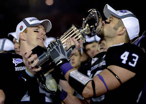 Photo - TCU quarterback Andy Dalton, left, holds the Rose Bowl trophy while TCU linebacker Tank Carder, right, kisses it after the Horned Frogs beat Wisconsin on Saturday. AP photo
