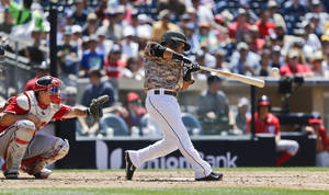 Photo - San Diego Padres' Alexi Amarista loops a line drive single for right field for the first Padres' hit against the Washington Nationals starting pitcher Jordan Zimmermann during the sixth inning of a baseball game Sunday, June 8, 2014, in San Diego. (AP Photo/Lenny Ignelzi)