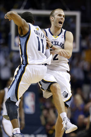 Photo - Memphis Grizzlies guard Mike Conley (11) celebrates with Nick Calathes, right, after Conley scored against the Miami Heat in the second half of an NBA basketball game Wednesday, April 9, 2014, in Memphis, Tenn. The Grizzlies won 107-102. (AP Photo/Mark Humphrey)