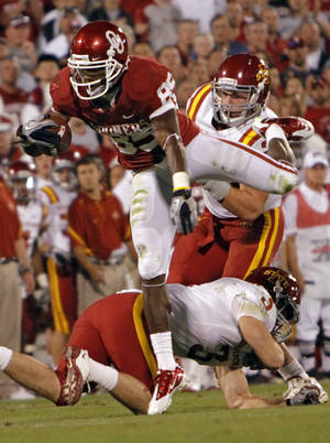 Photo - Oklahoma's Ryan Broyles (85) leaps over Iowa State's Zac Sandvig (3) during the first half of the college football game between the University of Oklahoma Sooners (OU) and the Iowa State Cyclones (ISU) at the Glaylord Family-Oklahoma Memorial Stadium on Saturday, Oct. 16, 2010, in Norman, Okla.  Photo by Chris Landsberger, The Oklahoman