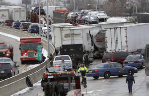 Photo - A section of multi-vehicle accident on Interstate 75 is shown in Detroit, Thursday, Jan. 31, 2013. Snow squalls and slippery roads led to a series of accidents that left at least three people dead and 20 injured on a mile-long stretch of southbound I-75. More than two dozen vehicles, including tractor-trailers, were involved in the pileups. (AP Photo/Paul Sancya)