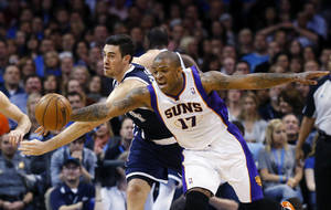 Photo - Oklahoma City Thunder forward Nick Collison, left, and Phoenix Suns forward P.J. Tucker (17) reach for the ball in the first quarter of an NBA basketball game in Oklahoma City, Monday, Dec. 31, 2012. (AP Photo/Sue Ogrocki)