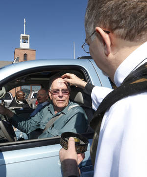 """Photo - The Rev. Tony Moon, right, a deacon at St. Augustine of Canterbury Episcopal Church, applies ashes to the forehead of Kenneth Ringer during the church's 2013 """"Ash and Dash"""" outreach outside the church at 14700 N May in Oklahoma City.  <strong>Sue Ogrocki - AP</strong>"""