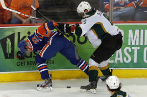 photo - Taylor Hall of the Oklahoma City Barons and Jamie Oleksiak of the Texas Stars fight or the puck during an AHL hockey game at the Cox Convention in Oklahoma City, Friday, Dec. 21, 2012. Photo by Bryan Terry, The Oklahoman
