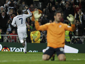Photo - Real Madrid's Cristiano Ronaldo from Portugal, left, celebrates his goal during a Spanish La Liga soccer match against Sevilla at the Santiago Bernabeu stadium in Madrid, Spain, Saturday, Feb. 9, 2013. (AP Photo/Andres Kudacki)