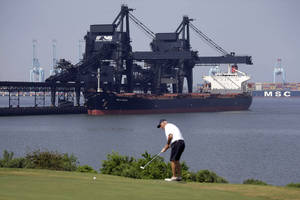 Photo - In this May 22, 2014, photo, a ship is docked at Norfolk Southern's Lamberts Point coal terminal as a man plays golf in Norfolk, Va. As the Obama administration weans the U.S. off dirty fuels blamed for global warming, energy companies have been sending more of America's unwanted energy leftovers to other parts of the world, where they could create even more pollution. (AP Photo/Patrick Semansky)