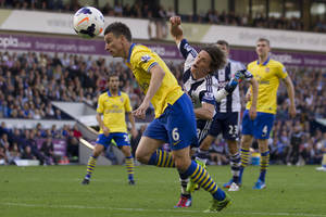 Photo - Arsenal's Laurent Koscielny, left, fights for the ball against West Bromwich Albion's Billy Jones, centre, during their English Premier League soccer match at The Hawthorns Stadium, West Bromwich, England, Sunday Oct. 6, 2013. (AP Photo/Jon Super)