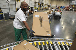 Photo - Leacroft Green works at an Amazon.com fulfillment center in Goodyear, Ariz. AP Photo