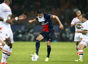 Photo - Paris Saint Germain's Edinson Cavani, center, controls  the ball during their French League One soccer match against Lorient, Friday Nov. 1, 2013, in Parc des Princes stadium, in Paris, France. (AP Photo/Jacques Brinon)