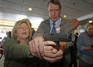 Photo - Christine Caldwell, left, receives firearms training with a 9mm Glock from personal defense instructor Jim McCarthy during concealed weapons training for 200 Utah teachers Thursday, Dec. 27, 2012, in West Valley City, Utah. The Utah Shooting Sports Council offered six hours of training in handling concealed weapons in the latest effort to arm teachers to confront school assailants. (AP Photo/Rick Bowmer)