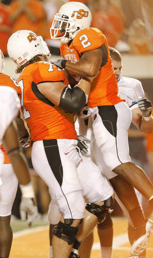 Photo - Noah Franklin, left, gives Beau Johnson a lift after his TD. Photo by Doug Hoke, The Oklahoman
