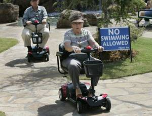 Photo - Charlotte and Ervin Wroblewski ride their scooters on Senior Citizens' Day at the 2010 Oklahoma State Fair. This year, seniors get free gate admission Sept. 21. Oklahoman Archive photo by Steve Gooch <strong>Steve Gooch</strong>