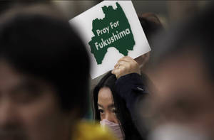 Photo - A protester holds a placard to pay tribute to the victims in Fukushima of the March 11, 2011 nuclear disaster following the earthquake and tsunami, during an anti-nuclear demonstration in Tokyo, Saturday, March 9, 2013. Gathering on a weekend ahead of the second anniversary of the March 11 quake and tsunami that sent Fukushima Dai-ichi plant into multiple meltdowns, demonstrators said they would never forget the world's worst nuclear catastrophe, and expressed alarm over the government's eagerness to restart reactors. (AP Photo/Junji Kurokawa)