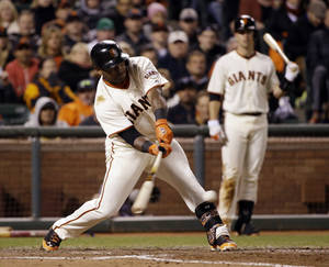 Photo - San Francisco Giants' Pablo Sandoval drives in a run with a single against the Los Angeles Dodgers during the seventh inning of a baseball game on Wednesday, April 16, 2014, in San Francisco. (AP Photo/Marcio Jose Sanchez)