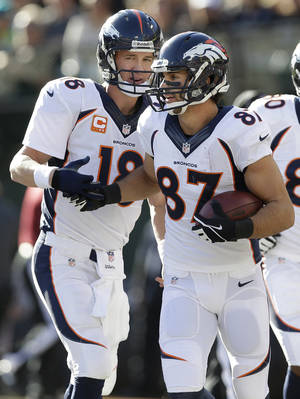 Photo - Denver Broncos quarterback Peyton Manning (18) celebrates with wide receiver Eric Decker (87) after connecting for a 3-yard touchdown pass against the Oakland Raiders during the first quarter of an NFL football game, Sunday, Dec. 29, 2013, in Oakland, Calif. (AP Photo/Marcio Jose Sanchez)