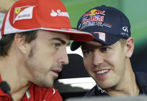 Photo -   Red Bull driver Sebastian Vettel, right, of Germany chats with Ferrari driver Fernando Alonso of Spain during the drivers press conference at the Korean International Circuit ahead of the Korean Formula One Grand Prix in Yeongam, South Korea, , Thursday, Oct. 11, 2012. (AP Photo/Lee Jin-man)