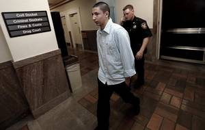 Photo - Sammie Chavez is escorted into a third floor courtroom, at the Washington County Courthouse Tuesday in Bartlesville. CORY YOUNG / Tulsa World