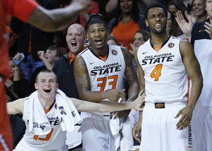 Photo - Oklahoma State guard Phil Forte (13), guard Marcus Smart (33) and wing Brian Williams (4) cheer on the bench following a dunk by teammate Le'Bryan Nash in the second half of an NCAA college basketball game against Texas Tech in Stillwater, Okla., Saturday, Feb. 22, 2014. Oklahoma State won 84-62. (AP Photo/Sue Ogrocki)