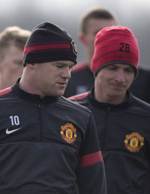 Photo - Manchester United's  Wayne Rooney, left, trains with teammates at Carrington training ground in Manchester, Monday, March 4, 2013. Manchester United will play Real Madrid in a Champion's League round of 16 soccer match on Tuesday. (AP Photo/Jon Super)