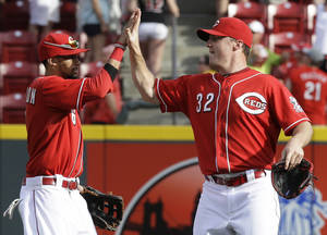 Photo - Cincinnati Reds right fielder Jay Bruce (32) high-fives center fielder Billy Hamilton after they defeated the Toronto Blue Jays 11-1 in a baseball game on Saturday, June 21, 2014, in Cincinnati. Bruce hit a home run in the game. (AP Photo/Al Behrman)
