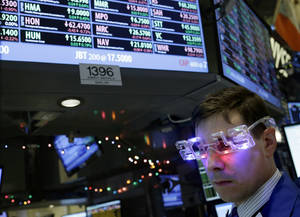 "photo - A trader wearing ""2013"" glasses works on the floor at the New York Stock Exchange in New York, Monday, Dec. 31, 2012.  The stock market struggled for direction Monday morning after five days of losses, with the ""fiscal cliff"" just hours away and lawmakers yet to reach a solution. (AP Photo/Seth Wenig)"