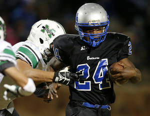 Photo - Guthrie's Idae Alexander brings tries to get past Tyler Kippenberger of Bishop McGuinness during their high school football game in Guthrie, Okla., Friday, November 1, 2013. Photo by Bryan Terry, The Oklahoman