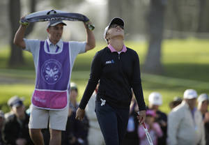Photo - Lydia Ko of New Zealand walks off the 18th green of the Lake Merced Golf Club after winning the Swinging Skirts LPGA Classic golf tournament on Sunday, April 27, 2014, in Daly City, Calif. Ko won the event after shooting a 3-under-par 69 to finish at 12-under-par. At left is her caddie Domingo Jojola. (AP Photo/Eric Risberg)