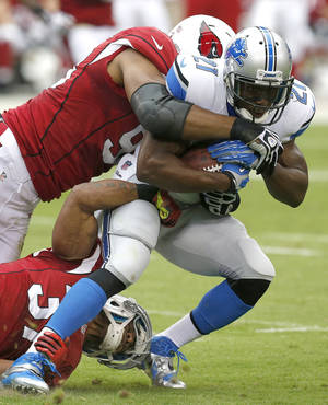 Photo - Detroit Lions running back Reggie Bush (21) is tackled by Arizona Cardinals defensive end Calais Campbell, left, and Yeremiah Bell, bottom, during the first half of a NFL football game, Sunday, Sept. 15, 2013, in Glendale, Ariz. (AP Photo/Ross D. Franklin)