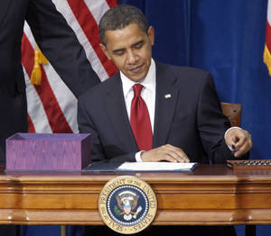Photo - FILE This Feb. 17, 2009 file photo shows President Barack Obama picking up the first pen to sign the economic stimulus bill during a ceremony in the Museum of Nature and Science in Denver. The White House says a costly spending bill President Barack Obama signed into law five years ago Monday was good for the economy and helped the U.S. avoid another Great Depression. (AP Photo/David Zalubowski, File)