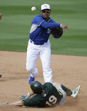 Photo - Oakland Athletics' Billy Burns (19) is forced out at second as Kansas City Royals' Christian Colon throws to first to complete a double play during the sixth inning of a spring exhibition baseball game on Friday, March 14, 2014, in Surprise, Ariz. (AP Photo/Darron Cummings)