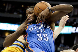 Photo - The Thunder's Kevin Durant grabs a rebound during the first quarter of Tuesday's game against the Nuggets.  AP Photo