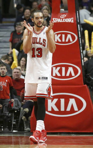 Photo - Chicago Bulls center Joakim Noah applauds his teammates during the second half of an NBA basketball game against the Boston Celtics, Thursday, Jan. 2, 2014, in Chicago. The Bulls won 94-82. (AP Photo/Charles Rex Arbogast)