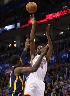 Photo - Oklahoma City Thunder forward Kevin Durant (35) shoots over Indiana Pacers forward Paul George (24) in the first quarter of an NBA basketball game in Oklahoma City, Sunday, Dec. 8, 2013. (AP Photo/Sue Ogrocki)