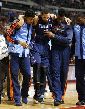 Photo - Charlotte Bobcats' Jeff Taylor is helped off the floor by teammates after being injured during the first half of an NBA basketball game against the Detroit Pistons in Auburn Hills, Mich., Friday, Dec. 20, 2013. (AP Photo/Paul Sancya)