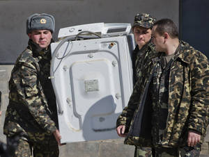 Photo - Ukrainian airmen carry a washing machine while removing their belongings from the Belbek air base, outside Sevastopol, Crimea, Friday, March 21, 2014. The base commander Col. Yuliy Mamchur said he was asked by the Russian military to turn over the base but is unwilling to do so until he receives orders from the Ukrainian defense ministry. (AP Photo/Vadim Ghirda)