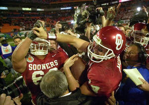 Photo - OU COLLEGE FOOTBALL, NATIONAL CHAMPIONSHIP: FOR USE WITH YEAR END STORIES Oklahoma quarterback Josh Heupel, right, is congratulated as he walks off the field with the game ball after beating Florida State 13-2 in the Orange Bowl Wednesday, Jan. 3, 2001 at Pro Player Stadium in Miami, Fla. (AP Photo/David F. Martin)