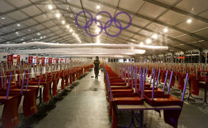 Photo - Seen through a plastic sheet with the Olympic ring logo, a woman cleans a large food court in the Olympic park during the 2014 Winter Olympics, early Saturday, Feb. 22, 2014, in Sochi, Russia. (AP Photo/Vadim Ghirda)