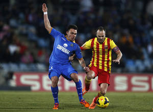 Photo - FC Barcelona's Andres Iniesta, right, in action with Getafe's Adrian Colunga during a Spanish La Liga soccer match between FC Barcelona and Getafe at the Coliseum Alfonso Perez stadium in Madrid, Spain, Sunday, Dec. 22, 2013. (AP Photo/Andres Kudacki)