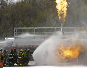 Photo - Firefighters spray fire suppressant foam to douse flames on a tanker truck in a simulated oil spill fire during a drill on Wednesday, May 7, 2014, in Albany, N.Y. Firefighters are getting some practice battling crude oil fires as part of stepped-up efforts by the Cuomo administration to address safety threats from increased rail shipment of highly flammable crude from North Dakota to East Coast refineries. The Port of Albany has become a major hub for crude oil transport, with oil trains arriving daily on routes that cross the state from the west and north. (AP Photo/Mike Groll)