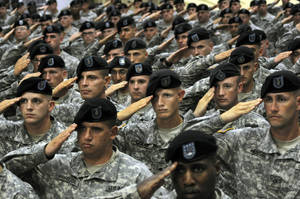 Photo - FILE - This July 28, 2010 file photo shows soldiers from the 10th Mountain Division saluting during the National Anthem during a welcome home ceremony attended by Vice President Joe Biden in Fort Drum, N.Y. In a massive restructuring, the U.S. Army is slashing the number of active duty combat brigades from 45 to 33, and shifting thousands of soldiers out of bases around the country as it moves forward with a longtime plan to cut the size of the service by 80,000.  The U.S. Army plans to eliminate one of three combat brigades at northern New York's Fort Drum.  (AP Photo/Heather Ainsworth, File)