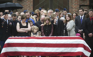 Photo - In this May 2, 2014 photo, family, friends and members of the military gather beside Kryn Miner's casket after his funeral outside St. Lawrence Church in Essex, Vt. His widow Amy Miner, third from left, believes the Veterans Affairs health system must do more to help veterans who struggle with Post Traumatic Stress Disorder after returning home. (AP photo/Burlington Free Press, Emily McManamy)