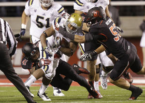 Photo - UCLA running back Jordon James, center,  carries the ball as Utah linebacker Jared Norris (41) and Utah linebacker Jason Whittingham (53) make a tackle in the second quarter during an NCAA college football game Thursday, Oct. 3, 2013, in Salt Lake City.   (AP Photo/Rick Bowmer)