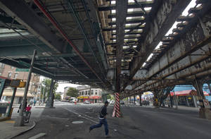 "Photo - A young man runs under an elevated section of subway tracks in The Bronx borough of New York,  Wednesday, May 22, 2013.  A company that offered tourist treks to the Bronx ""ghetto"" has shut down under scathing criticism from neighborhood leaders offended by the tours that took mostly European and Australian tourists past food-pantry lines and ""pickpocket"" park. But other New York companies continue to show visitors,  many of them foreigners who know of the Bronx only from movies, the grittiest part of the city's poorest borough. (AP Photo/Richard Drew)"