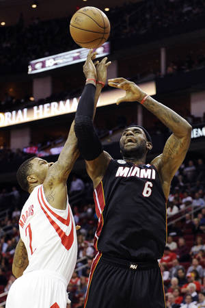 Photo -   Miami Heat's LeBron James (6) shoots while guarded by Houston Rockets' Marcus Morris (2) in the first half of an NBA basketball game, Monday, Nov. 12, 2012, in Houston. (AP Photo/Pat Sullivan)