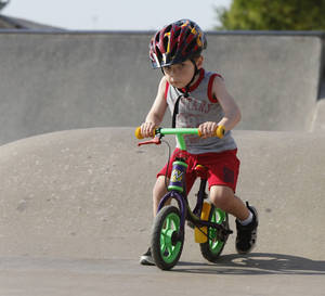 Photo - Ryan Johnson, 3, rides a bicycle at Mathis Brothers Skate Park in J.L. Mitch Park in Edmond. PHOTO BY PAUL HELLSTERN, THE OKLAHOMAN