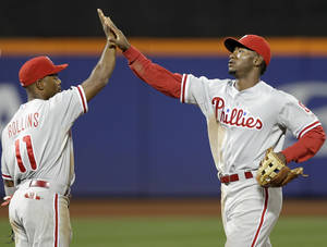 Photo -   Philadelphia Phillies' Jimmy Rollins (11) and Domonic Brown (9) celebrate their 3-1 victory over the New York Mets in their baseball game at Citi Field in New York, Monday, Sept. 17, 2012. (AP Photo/Kathy Willens)