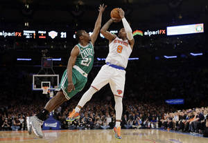 Photo - Boston Celtics guard Jordan Crawford (27) defends as New York Knicks guard J.R. Smith (8) shoots a 3-pointer in the first half of Game 2 of their first-round NBA basketball playoff series in New York, Tuesday, April 23, 2013. (AP Photo/Kathy Willens)