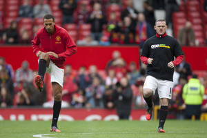 Photo -   Manchester United's Rio Ferdinand, left, is seen without an anti-racism shirt alongside teammate Wayne Rooney as the team warms up before their English Premier League soccer match against Stoke at Old Trafford Stadium, Manchester, England, Saturday, Oct. 20, 2012. (AP Photo/Jon Super)