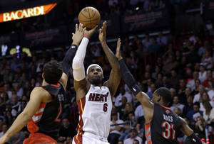 Photo - Miami Heat forward LeBron James (6) shoots against Toronto Raptors forward Landry Fields (2) and guard Terrence Ross (31) during the first half of an NBA basketball game on Wednesday, Jan. 23, 2013, in Miami. (AP Photo/Wilfredo Lee)