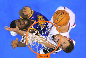 Photo - Los Angeles Clippers forward Blake Griffin, right, shoots against Golden State Warriors center Festus Ezeli, of Nigeria, during the first half of their NBA basketball game, Saturday, Jan. 5, 2013, in Los Angeles.  (AP Photo/Mark J. Terrill)